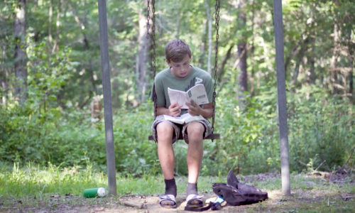 student holding a mission trip devotional