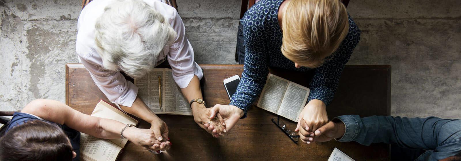praying intergenerational group at table